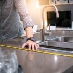 man measuring kitchen countertop